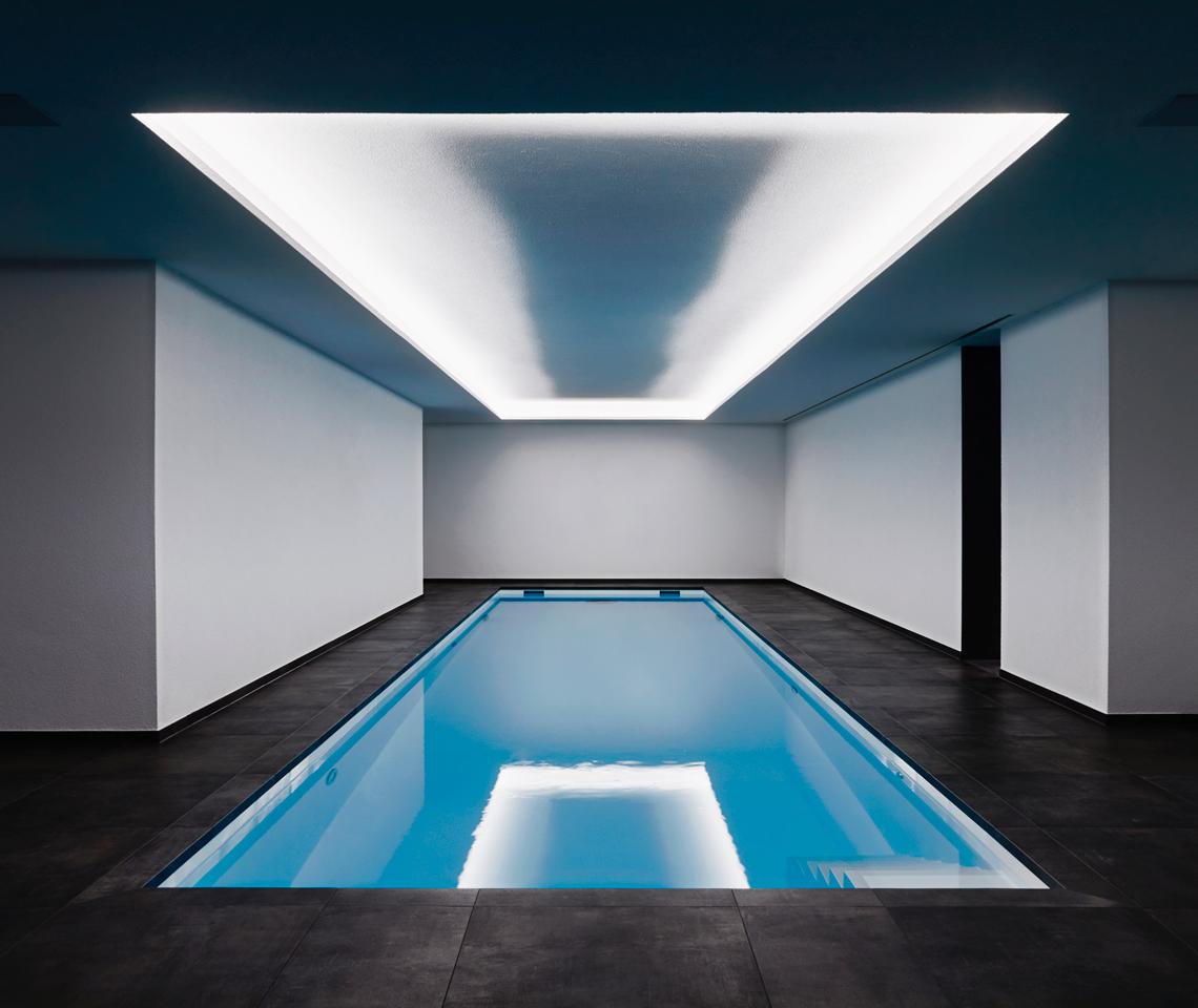 Auf dem Bild ist ein Pool zusehen der umgeben ist von weißen Wänden.Über dem Pool ist eine hell weiße decken Lampe.Um den Pool liegen schwarze Fliesen